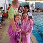 Lena und Vanessa, ganz in rosa getaucht, dahinter Trainer Dieter mit Bianca