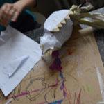 Die Schwanzfedern aus Zeitungspapier rollen und das untere Ende mit Malerkrepp fixieren und an den Körper kleben.