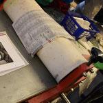Als Schutz vor der Farbe und der Feuchtigkeit des Papiers wird unter den Druck und über den Druck dünnes Papier gelegt