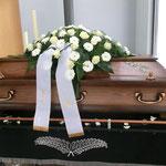 Sarg mit weißen Rosen und weißen Gerbera