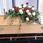 Sarg mit roten und weißen Rosen winterlich