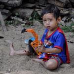 Junge im Sandkasten in der Parkanlage in den Bergen von Chian Mai