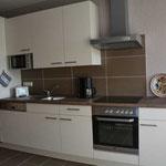 Die moderne Küche ist komplett ausgestattet.