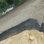 Böschung mit Erosionsschutz- und Krallmatte aus Kunststoff und Andeckung des Oberbodens