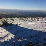 Der Brocken in winterlichem Weiß, das Umland in frühlingshaftem Grün