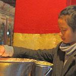 Junge Pilgerin im Drepung - Kloster, einem der ältesten Klöster von Tibet. Für die Götter wird Yakbutter geopfert.