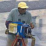 Fotograf vor dem Capitol in Havanna in Aktion. In diesem Kasten befindet sich auch die Chemie, in welcher das Bild gleich entwickelt wird.
