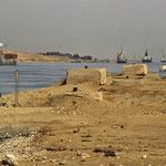 Eine Flotte mit mehreren Schiffen durchfährt den 1869 in Betrieb genommenen Suez-Kanal.