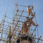Man kann fast nicht hinsehen, wenn in Schwindel erregender Höhe ein schaukliges Bambusgerüst aufgebaut wird.