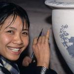 """Mädchen beim Bemalen einer Tonvase in einer Töpferei auf der Fahrt in die Halongbucht. Auf dem Boden der Vase stand: """"made in Vietnam for Ikea / Sweden"""""""