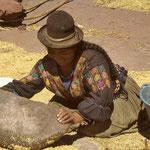 Indio-Frau am Titicacasee beim Mahlen von Getreide.