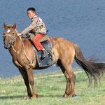 Mongolische Kinder wachsen auf dem Rücken der Pferde auf.
