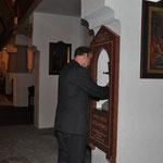 Der Leiter der Nagelkreuzgemeinschaft München, Walter Elsner, bringt andächtig das Nagelkreuz an seinen Platz