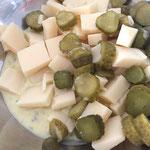 Käse und Cornichons mit der Salatsauce mischen