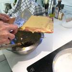 Den Teig portionenweise auf ein nasses Brett streichen