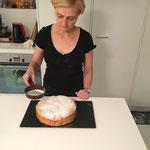 Den noch warmen Kuchen mit Puderzucker bestreuen