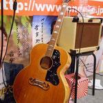 「GIBSON J-200」 エルビス・プレスリー、忌野清志郎が愛用していたギターとして知られる、ギブソン最高級モデルのひとつ。「口髭(ムスタッシュ)」と呼ばれる特徴ある形のブリッジ、分厚い胴から出る大音量に魅せられるミュージシャン憧れの1本。英祐一も以前からギブソンを使ってみたいという思いがありました。(2015年8月18日 札幌 音楽処インストア後に撮影)