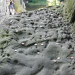 Es scheint, dass man die Münzen wohl vom Plateau des Grottenfels aus wirft. Soll das Glück bringen, oder einen Wunsch erfüllen? Wäre toll, wenn jemand was dazu sagen könnte.