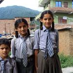 Alina und Pratikshya Luitel zusammen mit dem kleinen Bruder in Schuluniform