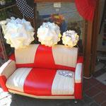 置物として使えるミニサイズのソファ。その上は波を打った形のランプ。