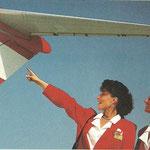 Werbeaufnahme mit zwei Flugbegleiterinnen, die auf das Leitwerk einer MD-80 zeigen/Courtesy: Austrian Airlines