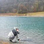 sylvain billot guide de pêche entrain de mettre une truite à l'épuisette