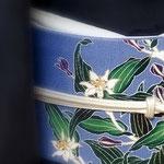芝崎重一さんの墨紺座繰り紬のきものに、ブルー地に「杜鵑」の花を描いた染め帯を合わせています。