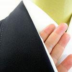 黒留袖、比翼仕立ての衿元。手のひらを差し込んで長襦袢に乗せる。