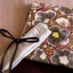 きものは浦野理一作の藤色の無地/縦節紬。鬼しぼ縮緬に椿の花を描いた浦野理一作袋帯。