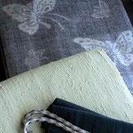 グレー地に白で蝶を織りだした縦節紬のきものに、ペパーミントグリーンの縦節の無地紬。どちらも浦野理一さんの作品です。