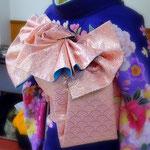 紺色に花柄の振袖と青海波文様のピンクの袋帯で、変わり結び「福来」を結んでいます。