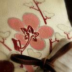 白地の縮緬にピンクの梅の花と枝が描かれた名古屋帯| 森口華弘さんの作品。