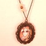 """Sautoir « La fille au cou tordu » Sautoir composé d'un magnifique médaillon bronze ajouré dans lequel est inclu un cabochon de verre avec une partie de l'illustration de Srinande """"La fille au cou tordu""""."""