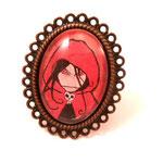 """Bague « La fille au chaperon rouge » Bague réglable couleur bronze garantie sans nickel sur laquelle est apposé un cabochon en verre avec un extrait de l'illustration de Srinande """"La Fille au chaperon rouge""""."""