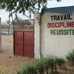 """Neben dem Eingangstor der Schule """"Grand MBour 1"""" stehen die Grundsätze ganz gross geschrieben."""