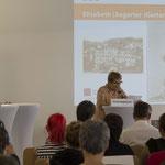 Im Hintergrund eine Präsentation mit Fotos von Elisabeth Gerter als Pflegerin.