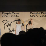 ファッションショーの間、パネルに文字や絵を描いています。