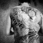 Tatouage d'un dragon serrant entre ses griffes une boule de cristal