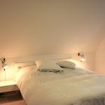 Schlafzimmer mit einem Doppelbett und Balkonzugang im Obergeschoß