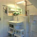 das Badezimmer im OG mit Badewanne, Dusche, Waschbecken, WC und Fußbodenheizung