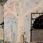Haupteingang des großen Luftschutzbunkers am Flugplatz. Die Wandmalereien dienten als Tarnung. Es sind noch die Einschüsse des Luftangriffes zu sehen