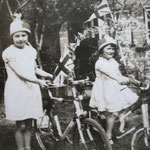 Pat Smith and her sister on bikes decorated for the Coronation in 1937