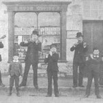 The Rose family outside their grocery business in Portland, Dorset, c. 1890. Henry Rose is third from the left, and his parents are extreme left and right.