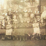A class has George Field next to Mr Rose, and he is marked with a red cross. The girl in white in the front row who is also marked with a red cross is George's sister, Doris Louisa Field. The date is probably also 1905.