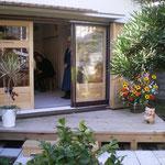 和室がギャラリーとなり、玄関横から庭を通り、ウッドデッキより中へ。