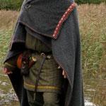 Der Rechteckmantel wurde mit einer Fiebel oder einer Nadel über einer Schulter geschlossen. Der umgeschlagene teil kann bei Regen als Kapuze über den Kopf gezogen werden. Sicher diente der Mantel auch oft als Decke beim Schlafen, wenn man unterwegs war.