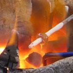Ein Eisenpin, der mit weißem Trennmittel vorbereitet ist wird zusammen mit einem Glasstab auf Temperatur gebracht