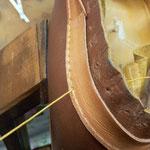 押し縁を本体を囲むように貼り付け手縫いしているところ