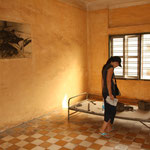 """In diesen """"Schulzimmern"""" wurden die Opfer von den Roten Khmers gefoltert. Ein Schwarz-Weiss-Foto zeigt die unvorstellbaren Gräueltaten. Die Opfer wurden zu Tode geprügelt um wertvolle Munition zu sparen."""