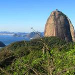 """Der """"Zuckerhut"""", ein Wahrzeichen Rio de Janeiros, ist ein 394 Meter hoher Granitfelsen, der der Stadt auf einer Halbinsel im Atlantik, in der Guanabara-Bucht gelegen, vorgelagert ist."""